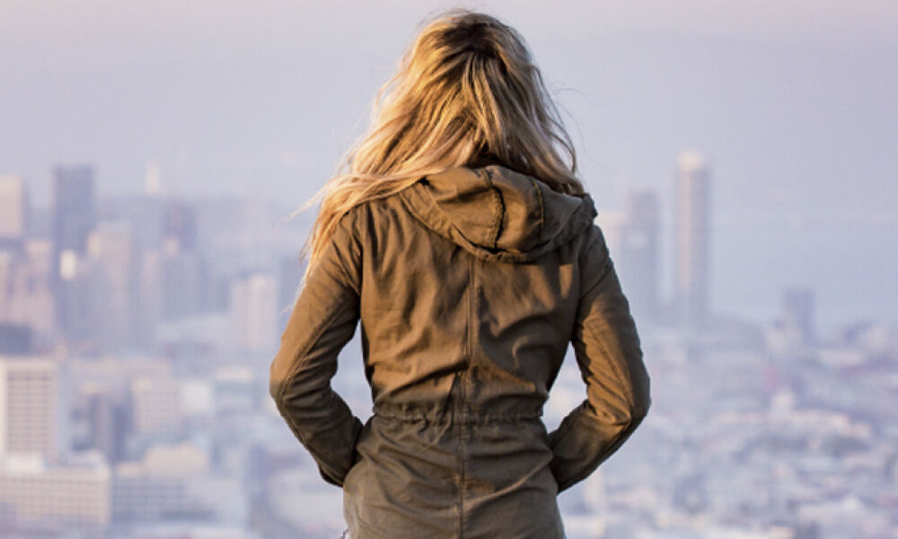 A photo of a woman looking at the city landscape