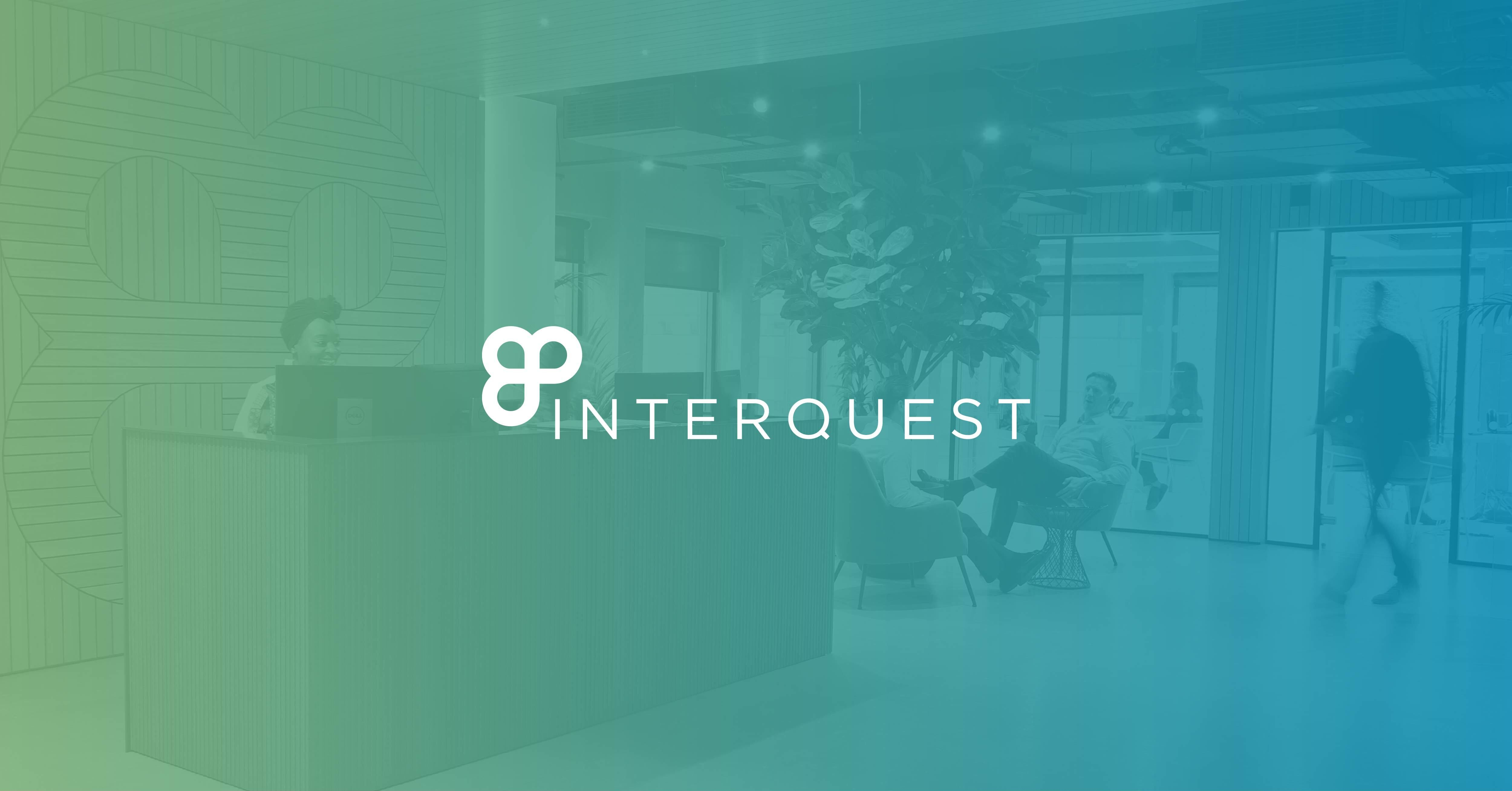 White InterQuest logo on a background image of InterQuest Group's reception area green and blue filter