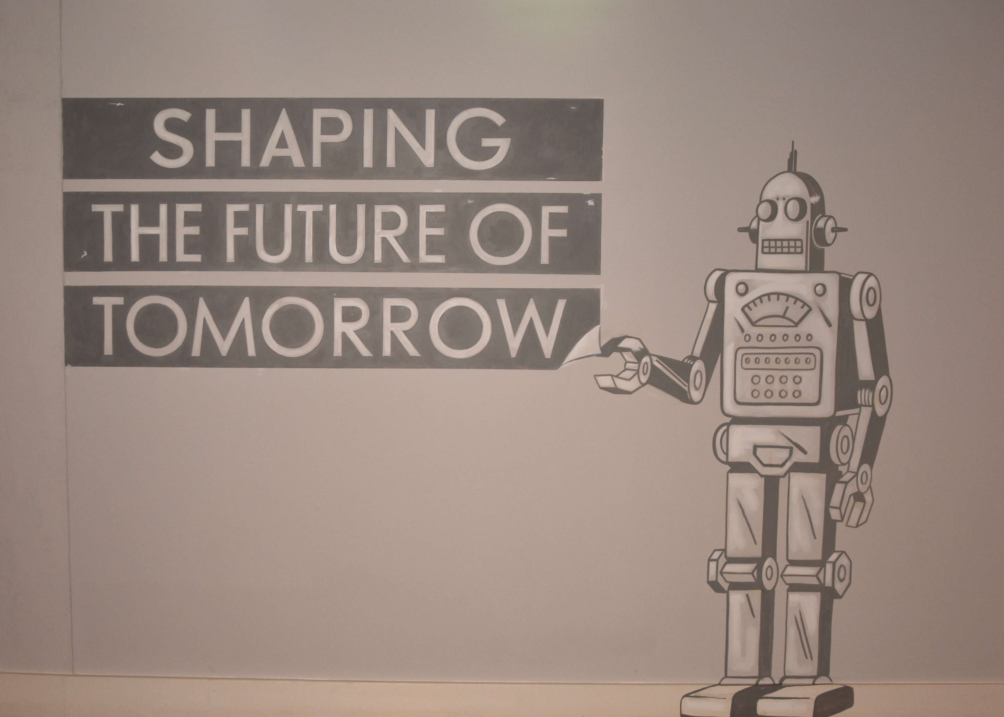 Shaping the future of tomorrow slogan on a wall illustration of a robot