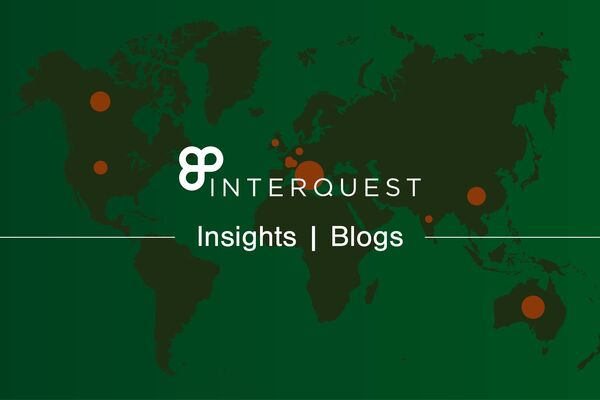White InterQuest logo on a grey-filtered background graphic of a green world map